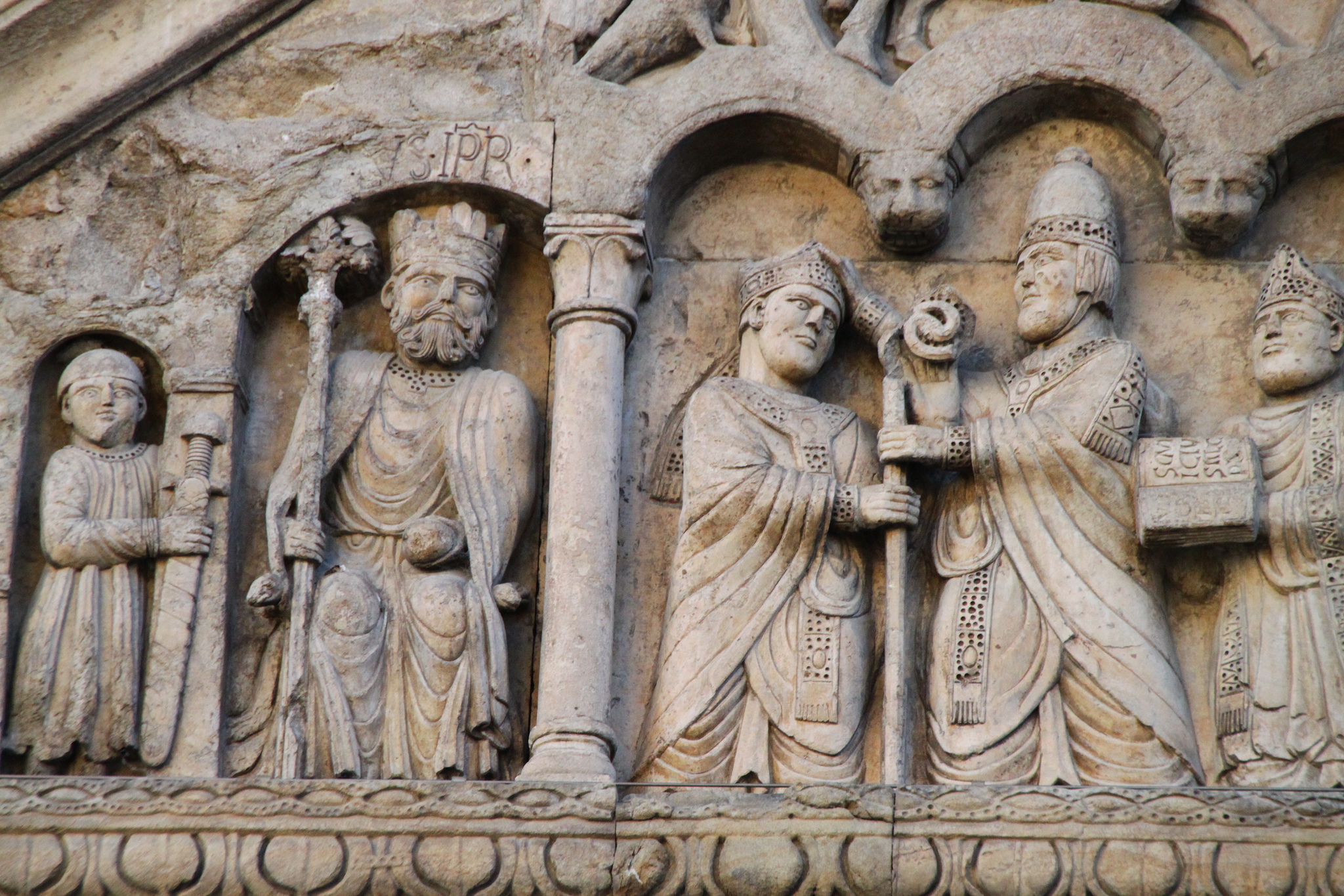 Charlemagne, name inscribed, crowned, seated, holding scepter in right hand and globe in left hand. Fidenza: Cathedral West Façade, north porch 1170-1220 attributed to Benedetto Antelami